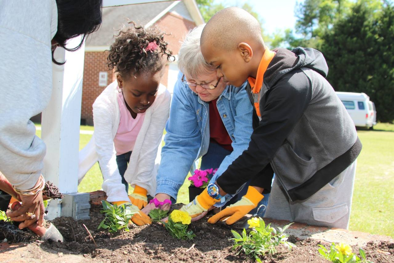 SM Susanne Dziedzic, Administrator at Felician Center, a Felician-Sponsored Ministry in Kingstree, South Carolina, shares the joy of after school learning with two community members.